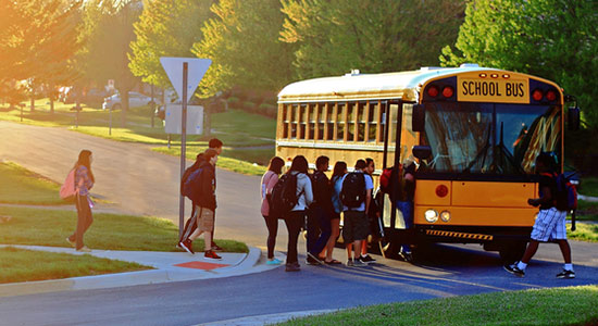 Kids getting on school bus.