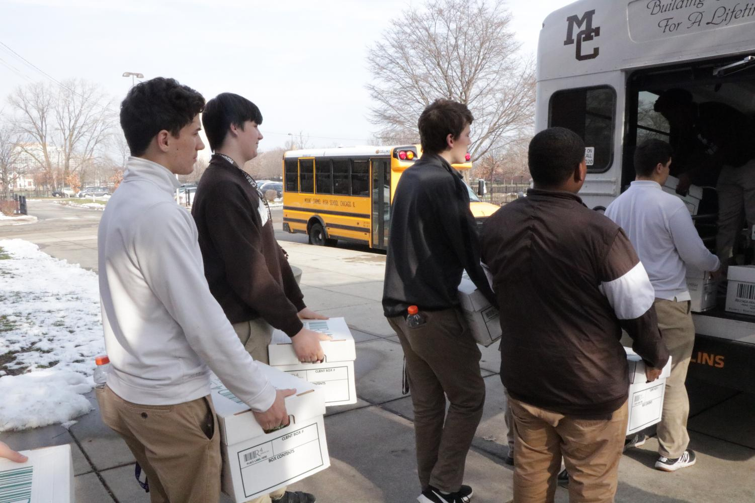 Students of Mr. McGuire's studium load the MC bus for their trip to Maple-Morgan Park Food Pantry