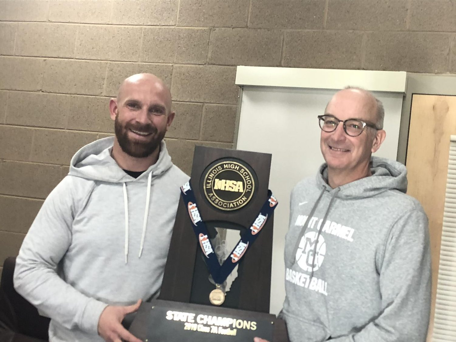 Head Coach Jordan Lynch and Athletic Director Dan LaCount are all smiles as they celebrate the schools 13th IHSA football championship.
