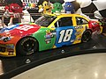 Kyle Busch's colorful #18 car is a familiar sight on the Nascar circuit. (Photo Credit via Wikimedia Commons under Creative Commons license)