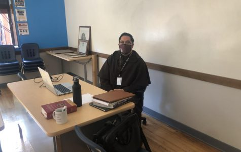Brother Ryan, a new member of the Theology Department, prepares for class on October 2 in Room 111. sitting in his classroom.
