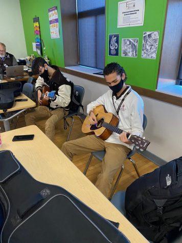 Seniors Ethan Hansen and Holden Shamala practice for their presentation exam in guitar class.