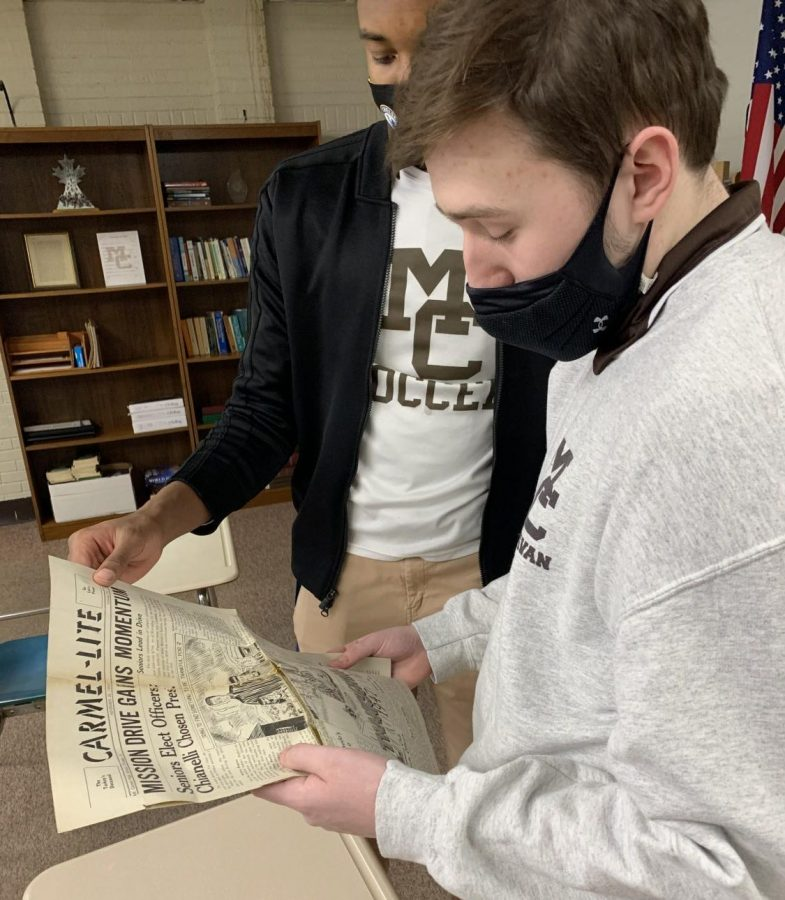 Ben Fields and Blayr Young, MC Caravan staff writers, look over vintage Carmel-lite newspapers from the late 1940's that were preserved for posterity by John Mills '48.