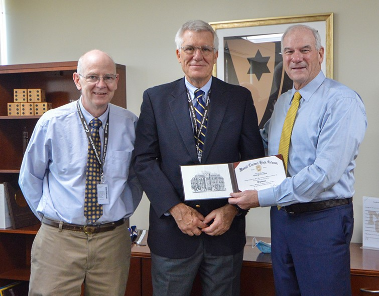 John Haggerty (left) arranged for George Vrechek to receive the million dollar diploma from Ned Hiughes (right).