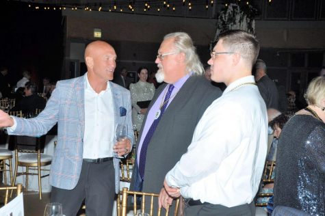 The two Mr. Novickases (center, right), current teachers at MC, speak with an alum at the 2021 Gala.